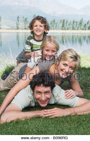 Familie mit zwei Kindern liegen auf dem Rasen, Menschenpyramide, Blick auf See - Stockfoto