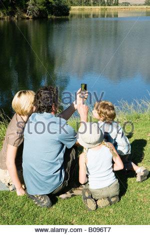 Junge Familie sitzen auf Rasen Blick auf Kompass und See, im freien - Stockfoto