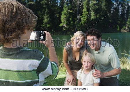 Junge Familie im Freien zu fotografieren, Mutter, Vater und Schwester posieren für Bild - Stockfoto