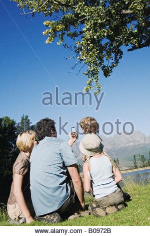 Junge Familie sitzen auf Rasen Kompass zeigt auf Berge, im Freien zu betrachten - Stockfoto