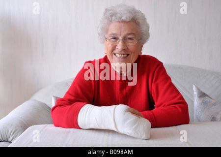Ältere Frau, ihre Rechte Hand in Gips - Stockfoto