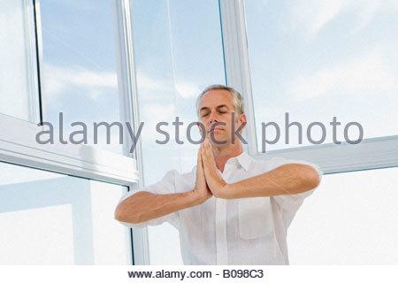 Senior woman sitzen, machen Yoga ausüben, im Innenbereich - Stockfoto