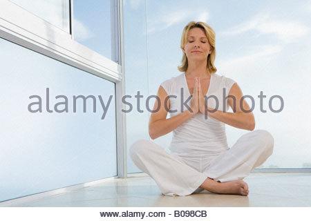 Ältere Frau sitzen, machen Yoga ausüben, im Innenbereich - Stockfoto