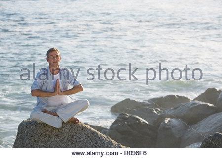 Reifen Mann sitzen tun Yoga auf Felsvorsprung mit Wellen im Hintergrund - Stockfoto