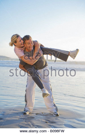 Ältere Paare, die Spaß am Strand, Mann mit Frau Huckepack - Stockfoto