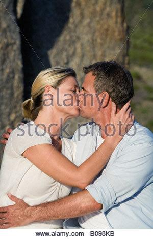 Älteres Paar sitzt auf Fels, umarmen und küssen, Porträt - Stockfoto