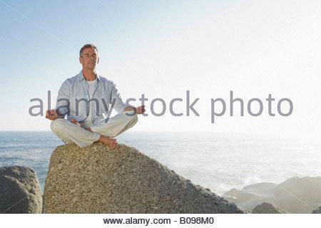 Reifen Mann sitzen tun Yoga-Übung auf Felsen mit Meer im Hintergrund - Stockfoto
