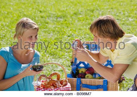 Junges Paar haben Picknick, Mann unter Foto Frau - Stockfoto