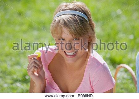 Junge Frau ein Picknick machen und Essen eine Traube, Porträt - Stockfoto