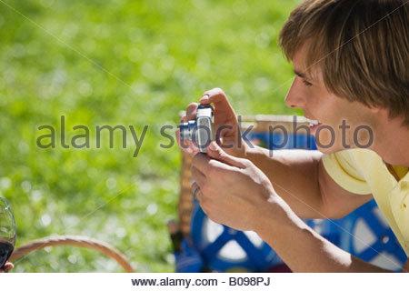 Junger Mann nehmen Foto mit Digitalkamera - Stockfoto