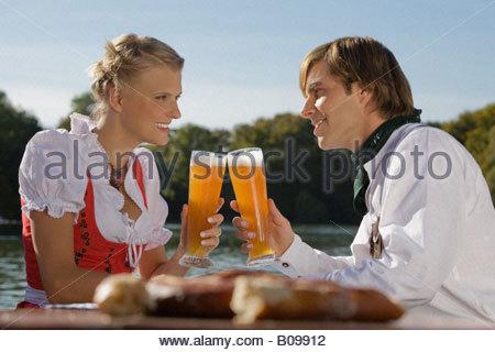Junges Paar in der traditionellen bayerischen Outfit, sitzt im Biergarten, München, - Stockfoto