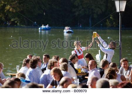 Junges Paar in der traditionellen bayerischen Outfit, toasten mit Biergläsern in Menge - Stockfoto
