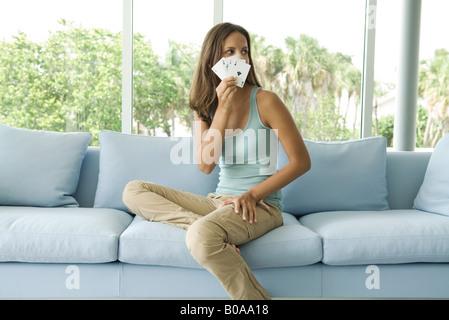 Teenager-Mädchen sitzen auf der Couch, mit Karten vor Gesicht, wegschauen - Stockfoto