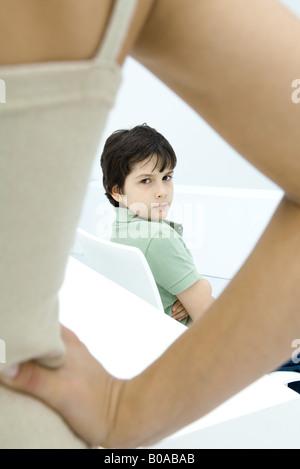 Junge, schmollen, auf der Suche über die Schulter bei Mutter im Vordergrund mit der Hand auf der Hüfte - Stockfoto