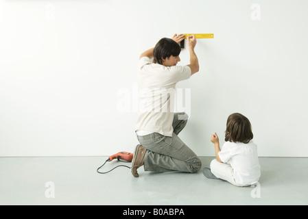 Mann Mess Wand mit einem Lineal während seines Sohnes Uhren, Bohren Sie auf dem Boden in der Nähe - Stockfoto