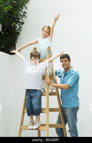 Jungen und Mädchen Vater Leiter, alle lächelnd in die Kamera hält auf Leiter mit den Armen in der Luft stehend - Stockfoto