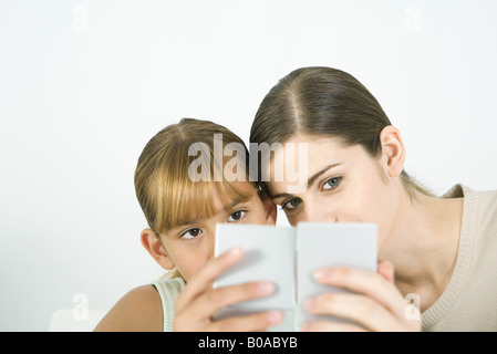 Frau und Mädchen Wange an Wange in die Hand Spiegel suchen - Stockfoto