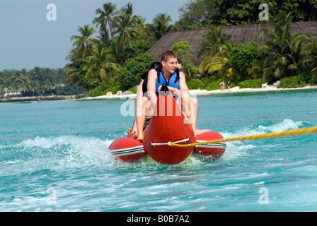 Vier Jugendliche, die Spaß am Urlaub auf Bananenboot fahren Kuramathi Island Malediven - Stockfoto