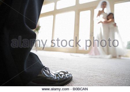 Braut und Brautjungfer umarmen neben Fenster, im Fokus des Bräutigams Schuh im Vordergrund, close-up Oberflächenniveau - Stockfoto