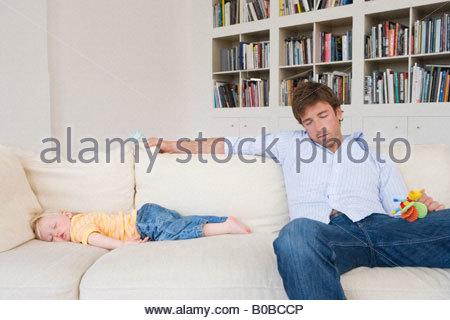 Vater und Tochter 12-15 Monate schlafend auf dem Sofa, Bücherregal im Hintergrund - Stockfoto