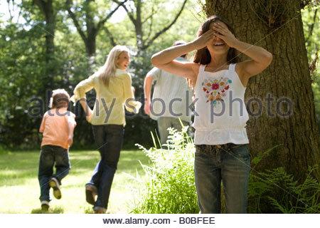 Familie von vier spielen im Wald, Mädchen, die Augen während der Familie laufen weg, niedrigen Winkel Ansicht bedecken - Stockfoto