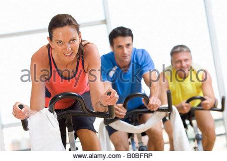 Menschen am Ergometer im Fitness-Studio, Lächeln, Porträt, niedrigen Winkel Ansicht - Stockfoto