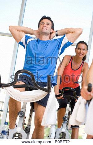 Mann mit Armen hinter Kopf am Ergometer im Fitness-Studio, im Hintergrund, niedrigen Winkel Ansicht lächelnde Frau - Stockfoto