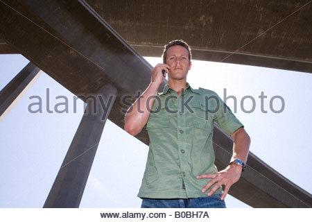 Junger Mann mit Handy unter Überführungen, hand auf Hüfte, niedrigen Winkel Ansicht - Stockfoto