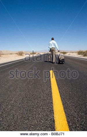 Geschäftsmann mit Gepäck unterwegs in der Wüste, Rückansicht - Stockfoto
