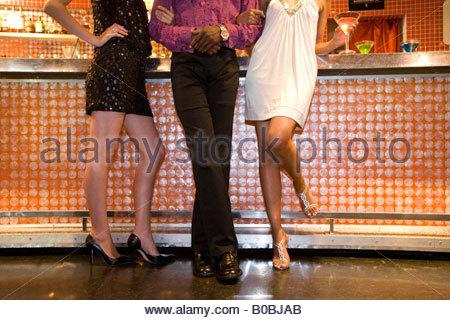 Mann, flankiert von Frauen in der bar, niedrige Abschnitt - Stockfoto