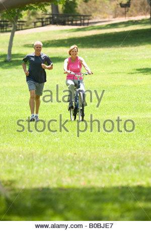 Reifer Mann von Frau auf Fahrrad im Park Joggen - Stockfoto
