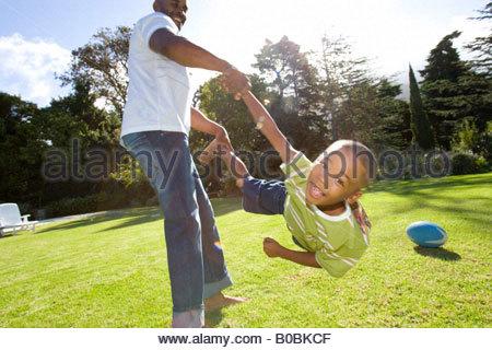 Vater schwingenden Sohn 6-8 Jahre in Luft im freien - Stockfoto