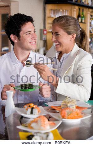 Junges Paar Lächeln einander im japanischen Restaurant, Frau mit Stäbchen - Stockfoto