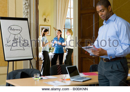 Gruppe von Unternehmerinnen Pause von Schulung, Mann auf Merkzettel schreiben - Stockfoto