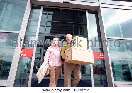 Älteres paar verlassen Shop mit Boxen, Lächeln einander, niedrigen Winkel Ansicht - Stockfoto