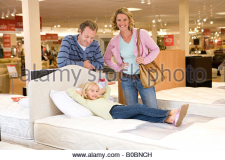 Familie mit drei im Möbelgeschäft, Tochter am Bett, Lächeln, Porträt - Stockfoto