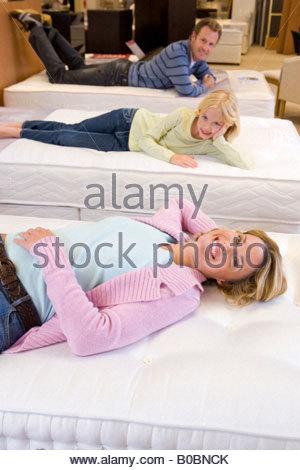 Familie mit drei Tests Betten im Möbelgeschäft, Lächeln, Porträt - Stockfoto