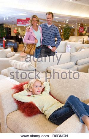 Familie von drei im Möbelgeschäft, Mädchen auf Sofa, Lächeln, Porträt - Stockfoto