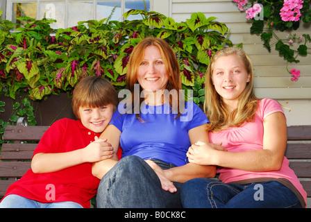 Porträt einer lächelnden Familie Mutter und Kinder vor dem Haus - Stockfoto