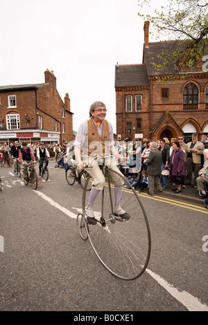 UK Cheshire Knutsford Royal Maifeiertag Prozession Mann reitet Hochrad Oldtimer Motorrad Gruppe - Stockfoto