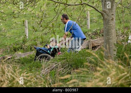 Vater schiebt behinderten Sohn im Rollstuhl auf dem Landweg durch die englische Landschaft - Stockfoto