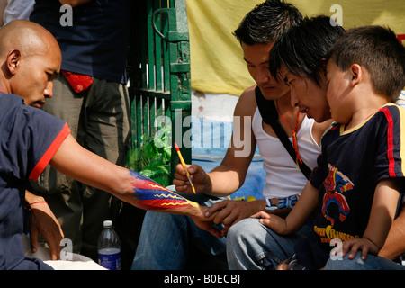 Ein Mann hat seinen Arm gemalt, während Menschen tibetischen Ursprungs im Bereich Janpath in Neu-Delhi, Indien zu - Stockfoto