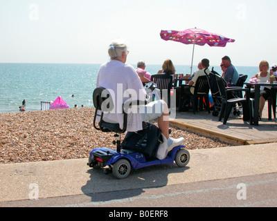 ältere Frau am Meer genießen und Fortbewegung auf elektronische motorisierte Roller Bognor Regis West Sussex - Stockfoto