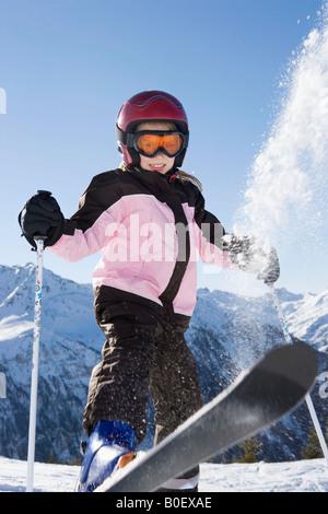 Junges Mädchen flicking Schnee von ihrem Ski - Stockfoto