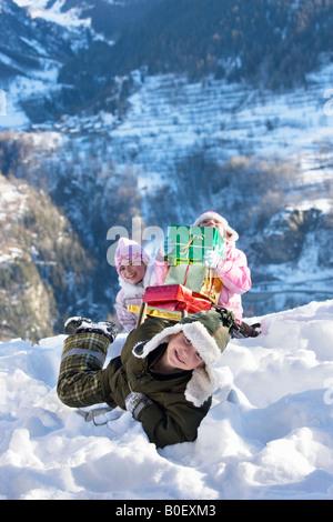 Kinder spielen im Schnee mit präsentiert - Stockfoto