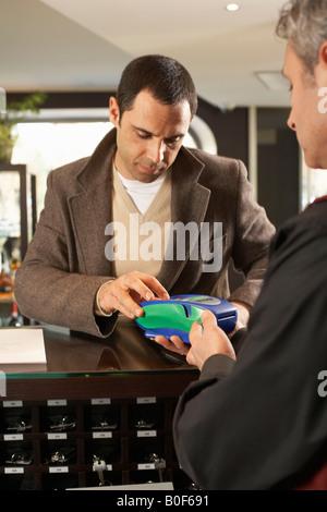 Hotelgäste, die Zahlung per Kreditkarte - Stockfoto