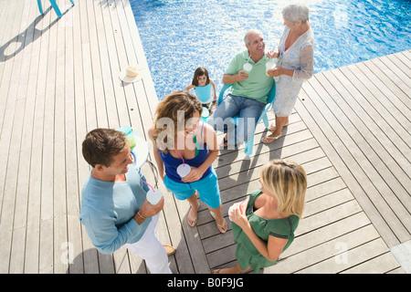 Familie auf einer Holzterrasse am pool - Stockfoto