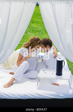 Paar beim Frühstück am Bett im Garten - Stockfoto