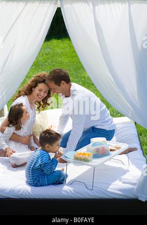 Familie frühstücken im Bett im Garten - Stockfoto