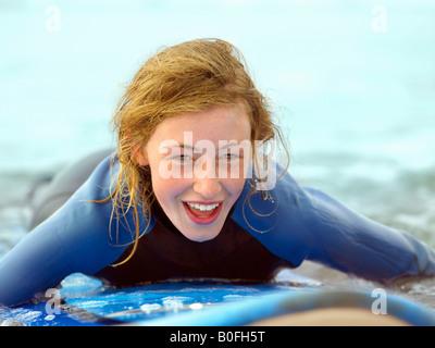 Weibchen auf Surfbrett nehmen kleine Welle - Stockfoto